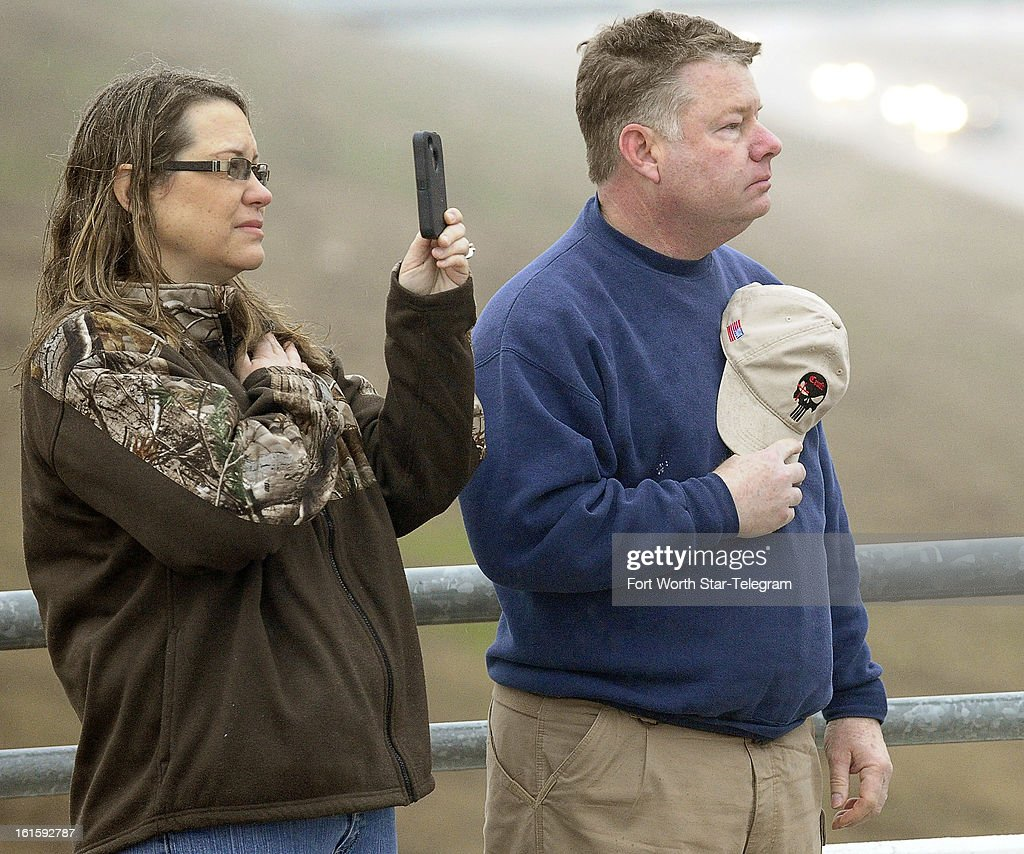 Tracy, right, and Lucinda Larimore, of Henderson, Nevada, friends of Chris Kyle, pay their respects as the funeral procession passed on US 287 in Midlothian, Texas, Tuesday, February 12, 2013. A motorcade of about 200 vehicles accompanied the white hearse carrying Kyle's flag-draped coffin on the 200-mile journey to Austin, where he will be buried at the Texas State Cemetery.
