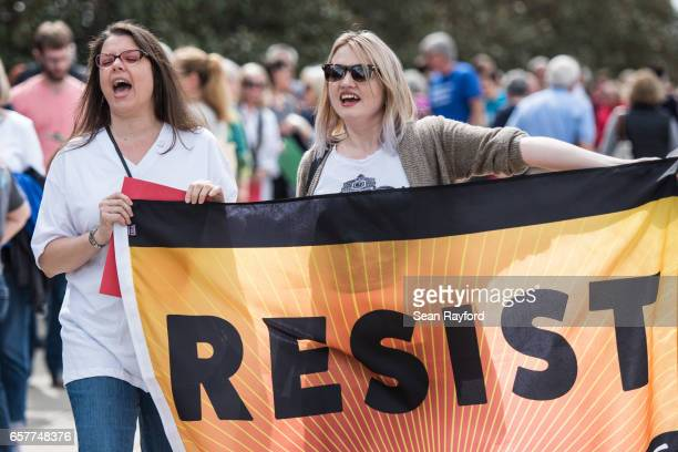 Tracy Simpson and Caitlin Velazquez voice their displeasure for President Donald Trump before a town hall meeting with Sen Lindsey Graham March 25...