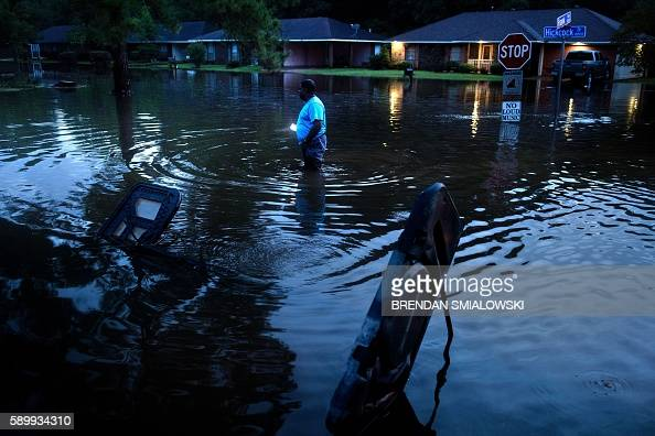 TOPSHOT Tracy Thornton walks to his house through a flooded neighborhood August 15 2016 in Baton Rouge Louisiana Floods ravaged the US state of...