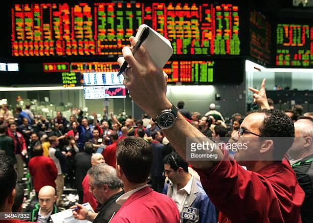 Trader Andrew Friedman right signals trades in the SP 500 pit at CME Group Inc's Chicago Board of Trade shortly before the Federal Open Market...