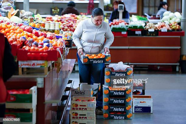 A trader arranges boxes of fresh fruit and oranges at her stall inside the city's covered central market former Zeppelin hangars from the First World...