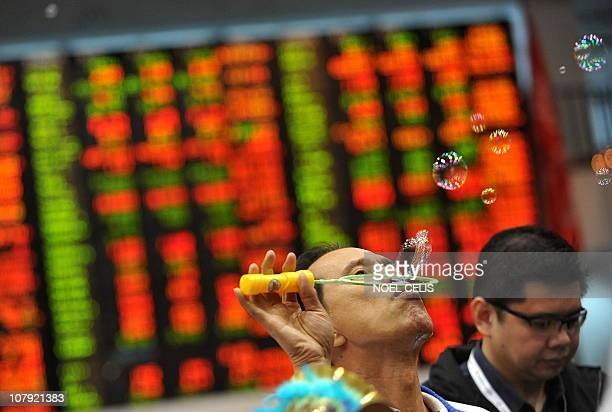 A trader blows bubbles during the yearend closing of trade in front of a giant electronic board at the Philippine Stock Exchange in Manila on...