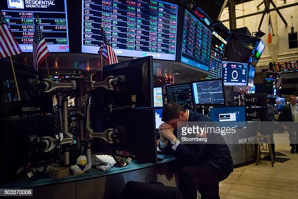 A trader bows his head while working on the floor of the New York Stock Exchange in New York US on Monday Jan 4 2016 US stocks tumbled to start 2016...
