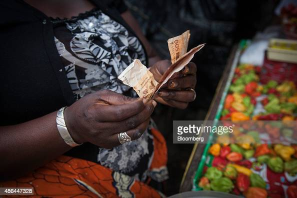 A trader counts out CFA West African franc banknotes on her food stall at a market in Abidjan Ivory Coast on Wednesday Sept 2 2015 The stability from...