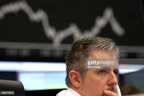 Trader Dirk Mueller works as the DAX index curve is displayed on a screen behind him at the Deutsche Boerse AG in Frankfurt Germany on Wednesday Jan...