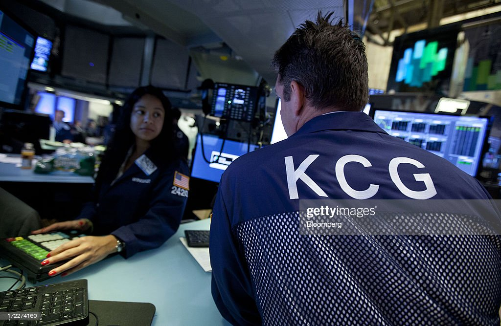 A trader from KCG Holdings Inc., right, the new company formed by the merger between Getco LLC and Knight Capital Group Inc., works at the New York Stock Exchange (NYSE) in New York, U.S., on Tuesday, July 2, 2013. Getco LLC and Knight Capital Group Inc. completed their merger, creating a public company that will play one of the biggest roles in the daily functioning of the U.S. stock market. The new company, KCG Holdings Inc., began trading today at the NYSE. Photographer: Jin Lee/Bloomberg via Getty Images