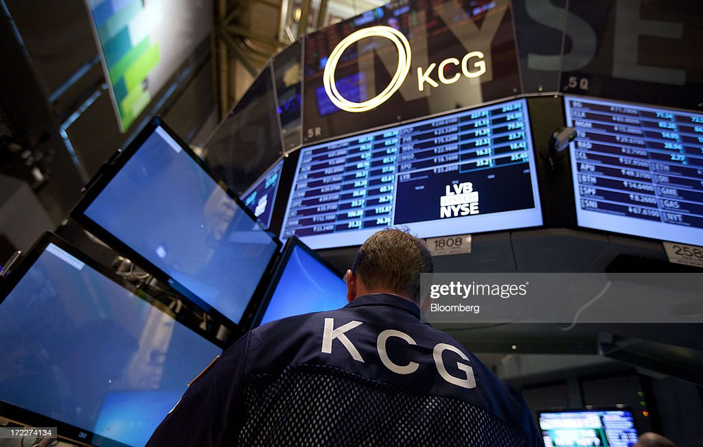 A trader from KCG Holdings Inc., the new company formed by the merger between Getco LLC and Knight Capital Group Inc., works at KGC's trading post at the New York Stock Exchange (NYSE) in New York, U.S., on Tuesday, July 2, 2013. Getco LLC and Knight Capital Group Inc. completed their merger, creating a public company that will play one of the biggest roles in the daily functioning of the U.S. stock market. The new company, KCG Holdings Inc., began trading today at the NYSE. Photographer: Jin Lee/Bloomberg via Getty Images