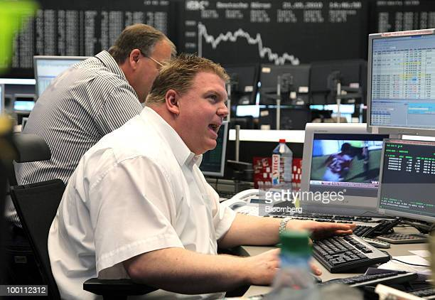 Trader Georg Hinkel works at his computer screen against the backdrop of the DAX index curve at the Frankfurt Stock Exchange in Frankfurt Germany on...