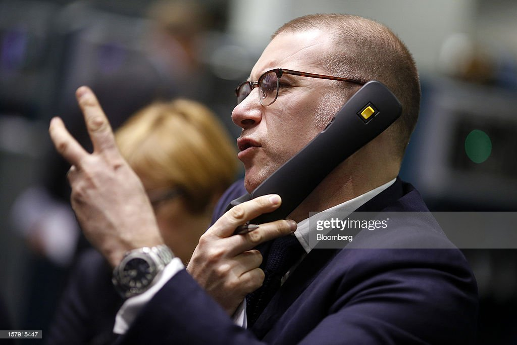 A trader gestures as he speaks on a telephone during trading on the floor of the London Metal Exchange (LME) in London, U.K., on Friday, Dec. 7, 2012. The London Metal Exchange's $2.2 billion takeover by the Hong Kong Exchanges & Clearing Ltd. was completed yesterday. Photographer: Simon Dawson/Bloomberg via Getty Images