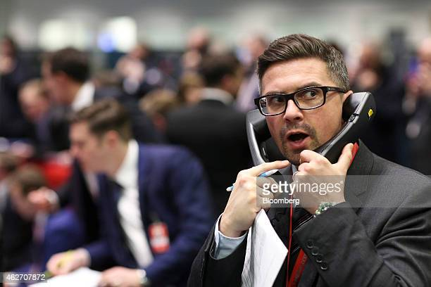 A trader gestures as he speaks on telephones on the trading floor outside the open outcry pit at the London Metal Exchange in London UK on Tuesday...