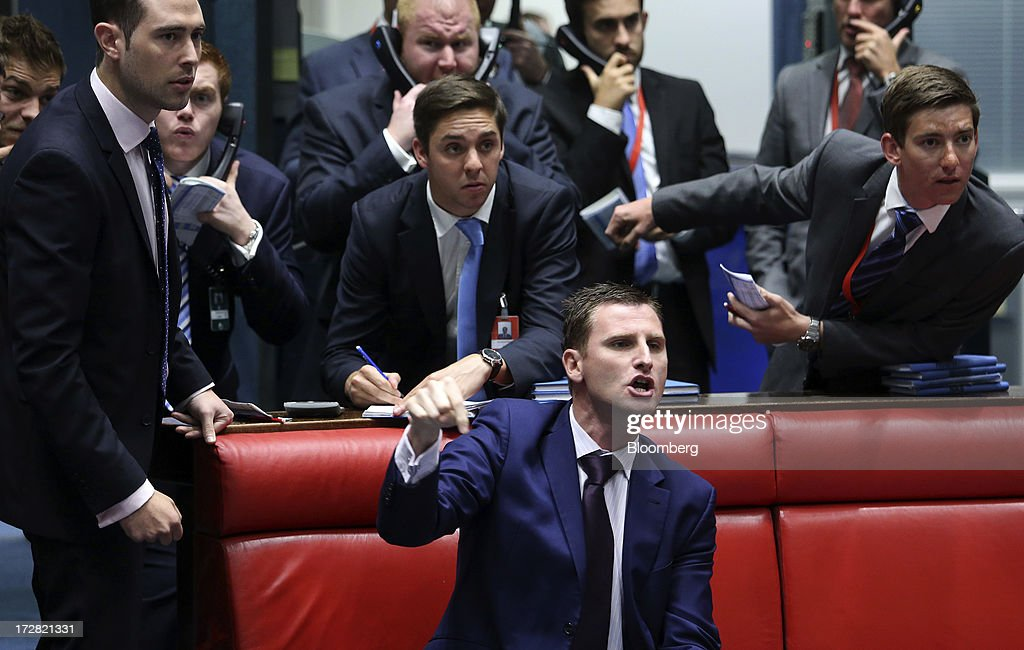 A trader gestures from inside the open outcry pit as he works on the trading floor of the London Metal Exchange (LME) in London, U.K., on Wednesday, July 3, 2013. The London Metal Exchange's proposal to speed up deliveries of metal from its approved warehouses may lower aluminum and zinc premiums, Macquarie Group Ltd. said. Photographer: Chris Ratcliffe/Bloomberg via Getty Images