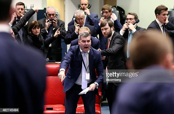 A trader gestures from inside the open outcry pit as he works on the trading floor at the London Metal Exchange in London UK on Tuesday Feb 3 2015...