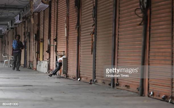 A trader gets in through his half shuttered shop during the nationwide shutdown to protest GST at Tripoliya on June 30 2017 in Jaipur India The...