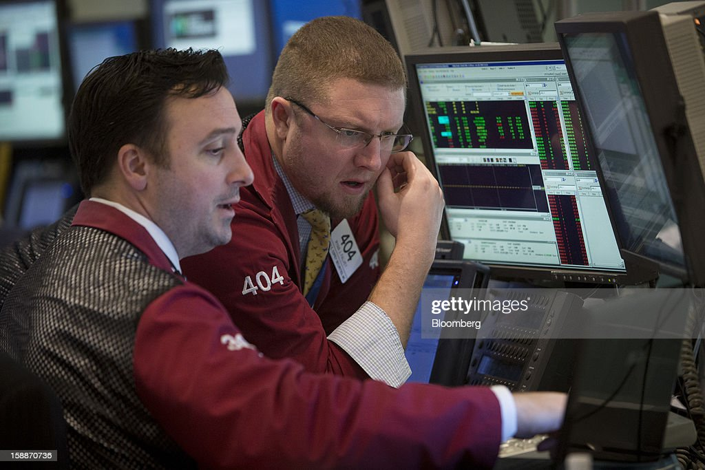 Trader interact while working on the floor of the New York Stock Exchange (NYSE) in New York, U.S., on Wednesday, Jan. 2, 2013. U.S. stocks rose, after the largest year-end rally for the Standard & Poor's 500 Index since 1974, as lawmakers passed a bill averting spending cuts and tax increases threatening a recovery in the world's biggest economy. Photographer: Scott Eells/Bloomberg via Getty Images