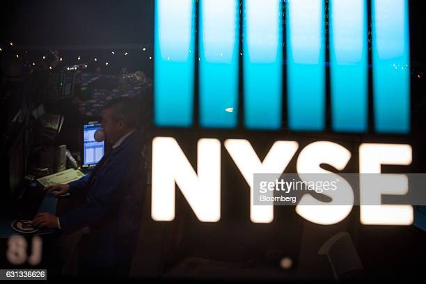 A trader is reflected in signage displayed at the New York Stock Exchange in New York US on Monday Jan 9 2017 US stocks declined Monday as investors...