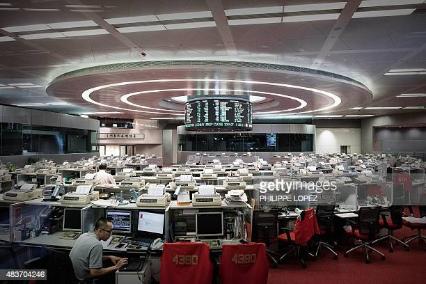 A trader is seen on the floor of the Hong Kong Stock Exchange on August 12 2015 Asian shares tumbled on August 12 as investors fretted over the...