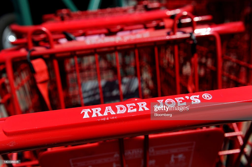 Trader Joe's Co. logo is displayed on shopping carts outside of a store in Emeryville, California, U.S., on Friday, Sept. 13, 2013. Trader Joe's Co., the closely held grocery store chain, will end health benefits for part-time workers next year, directing them instead to anew insurance marketplaces as companies revamp medical coverage to fit the U.S. Affordable Care Act. Photographer: David Paul Morris/Bloomberg via Getty Images