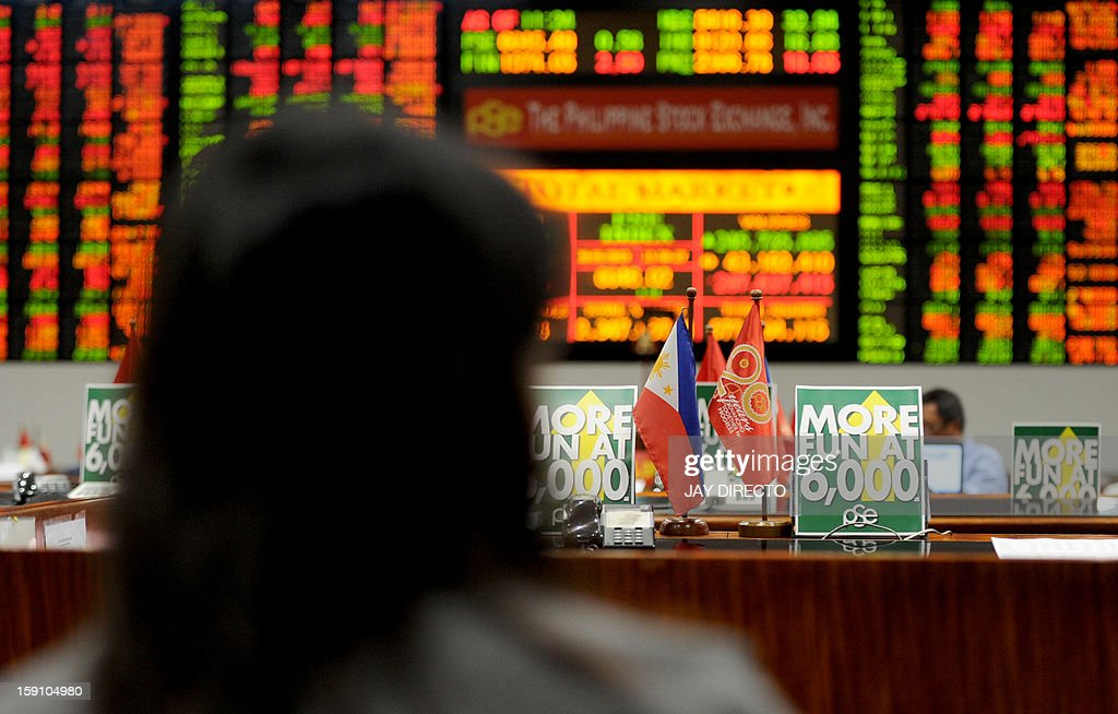 A trader looks at a stocks monitor at the Philippine Stock Exchange in Manila on January 8, 2013. Share prices hit new record closing highs in the first five trading days of the year and are up four percent compared to end-2012. AFP PHOTO / Jay DIRECTO