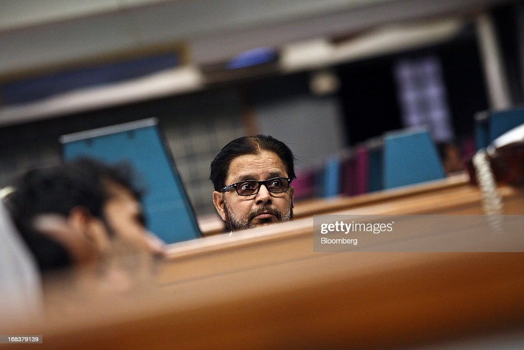 A trader looks at an electronic screen displaying stock prices, unseen, in the trading hall of the Karachi Stock Exchange in Karachi, Pakistan, on Wednesday, May 8, 2013. Pakistan is to hold parliamentary elections on May 11. According to opinion polls, Nawaz Sharif of the Pakistan Muslim League-N (PMLN) leads Imran Khan of Pakistan Tehrik-e-Insaf (PTI) in the race to replace president Asif Ali Zadari and become Pakistan's 12th president. Photographer: Asim Hafeez/Bloomberg via Getty Images