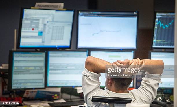 A trader looks at computer screens as the day's performance graph showed a sharp drop of the German DAX stock market index early today and a partial...