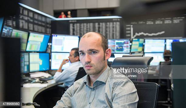 A trader looks at computer screens as the day's performance graph shows a sharp drop of the German DAX stock market index early today and a partial...