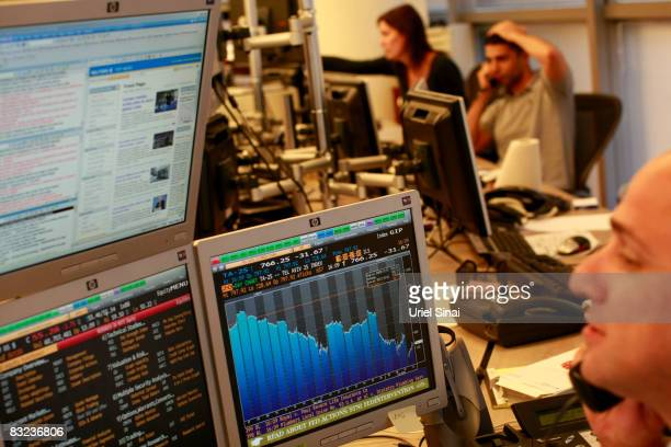 A trader looks at his monitors as he works in a dealing room in Tel Aviv on October 12 2008 in Tel Aviv Israel Israeli shares plunged by over 8...