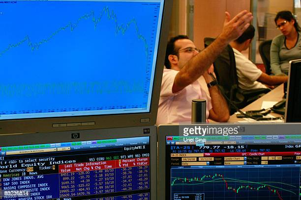 A trader looks gestures as he works in a dealing room in Tel Aviv on October 12 2008 in Tel Aviv Israel Israeli shares plunged by over 8 percent on...