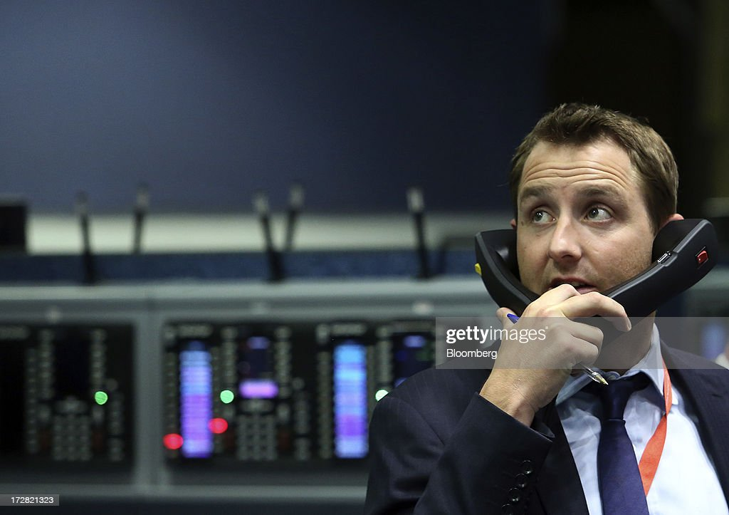 A trader looks towards a digital display board while speaking on telephones from the trading floor of the London Metal Exchange (LME) in London, U.K., on Wednesday, July 3, 2013. The London Metal Exchange's proposal to speed up deliveries of metal from its approved warehouses may lower aluminum and zinc premiums, Macquarie Group Ltd. said. Photographer: Chris Ratcliffe/Bloomberg via Getty Images
