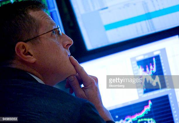 A trader looks up at a monitor while working on the floor of the New York Stock Exchange in New York US on Monday July 13 2009 US stocks rallied...