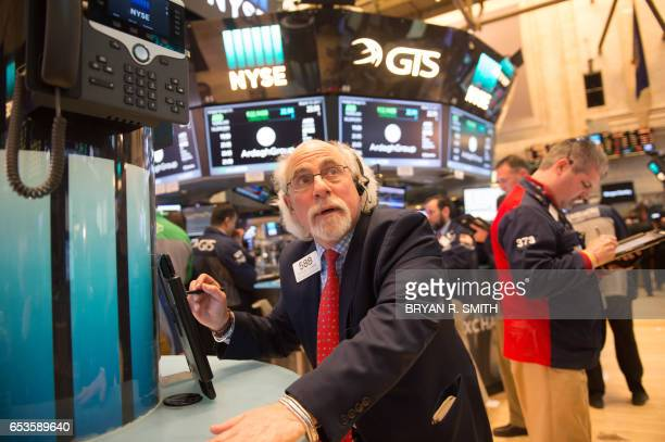 A trader looks up before the closing bell of the Dow Jones at the New York Stock Exchange on March 15 2017 in New York US stocks added to gains and...