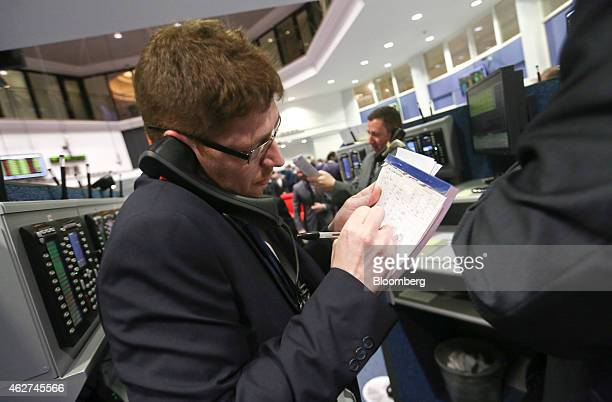 A trader makes notes whilst speaking on a telephone as he works on the trading floor outside the open outcry pit at the London Metal Exchange in...