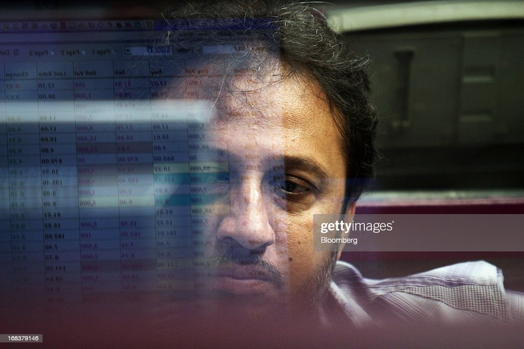 A trader monitoring stocks is reflected on a computer screen at the Karachi Stock Exchange in Karachi, Pakistan, on Wednesday, May 8, 2013. Pakistan is to hold parliamentary elections on May 11. According to opinion polls, Nawaz Sharif of the Pakistan Muslim League-N (PMLN) leads Imran Khan of Pakistan Tehrik-e-Insaf (PTI) in the race to replace president Asif Ali Zadari and become Pakistan's 12th president. Photographer: Asim Hafeez/Bloomberg via Getty Images