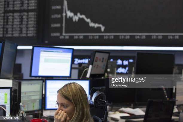 A trader monitors financial data as the DAX index curve is displayed beyond following the the election of Emmanuel Macron as France's new president...