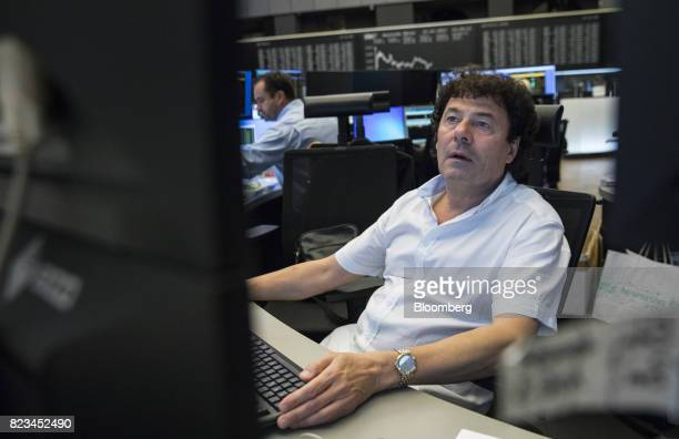 A trader monitors financial data inside the Frankfurt Stock Exchange operated by Deutsche Boerse AG in Frankfurt Germany on Thursday July 27 2017...