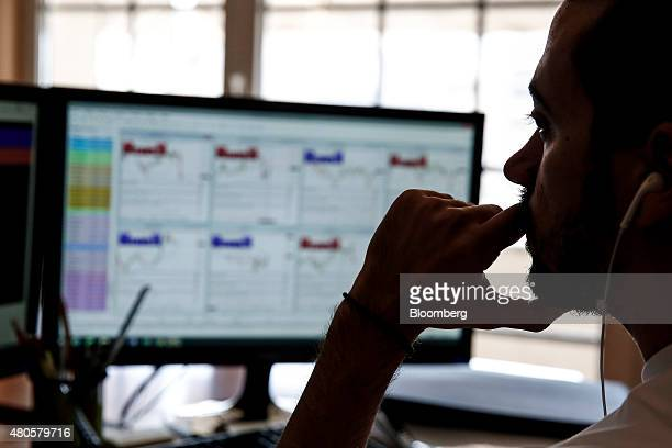 A trader monitors financial data on a computer screen inside the offices of Nuntius Securities SA brokers in Athens Greece on Monday July 13 2015...