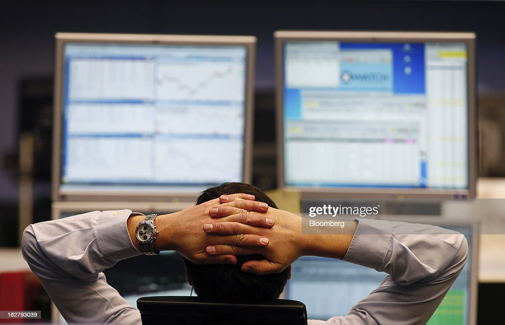 A trader monitors financial data on his computer screens as he works inside the Frankfurt Stock Exchange in Frankfurt, Germany, on Tuesday, Feb. 27, 2013. Stocks rose, the euro strengthened from a seven-week low and Italian 10-year bonds gained after the country sold 6.5 billion euros ($8.5 billion) of debt amid political turmoil. Photographer: Ralph Orlowski/Bloomberg via Getty Images