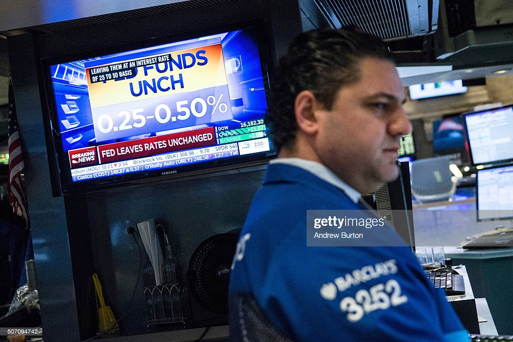 A trader on the floor of the New York Stock Exchange reacts to the news that the Federal Reserve will not raise interest rates during the afternoon...
