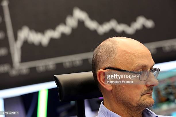 A trader on the trading floor of the Frankfurt Stock Exchange as a graph shows the day's performance of the DAX index the day after the 'NO' vote in...