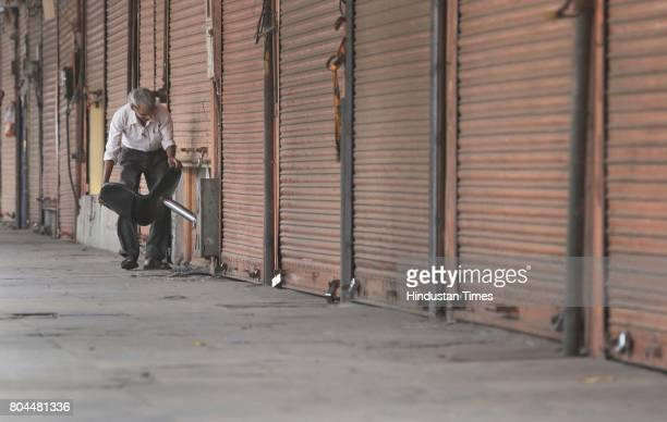 Trader passes a chair through half closed shutter of shop during the nationwide shutdown to protest GST on June 30 2017 in Jaipur India The traders...