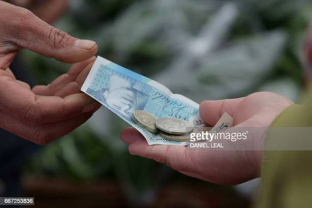 A trader passes a customer their change in the form of a five pound sterling note and one and two pound coins at Whitechapel Market in east London on...