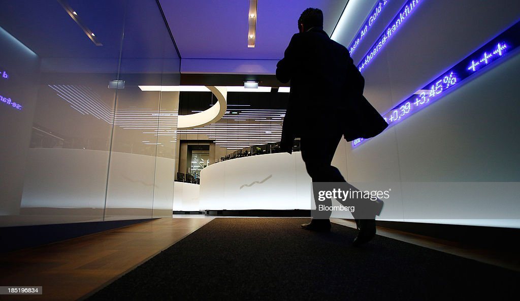 A trader passes an electronic display board as he enters the trading floor at the Frankfurt Stock Exchange in Frankfurt, Germany, on Friday, Oct. 18, 2013. Global stocks rose for a third day, extending a five-year high, and copper climbed after China's economic growth quickened. Photographer: Ralph Orlowski/Bloomberg via Getty Images