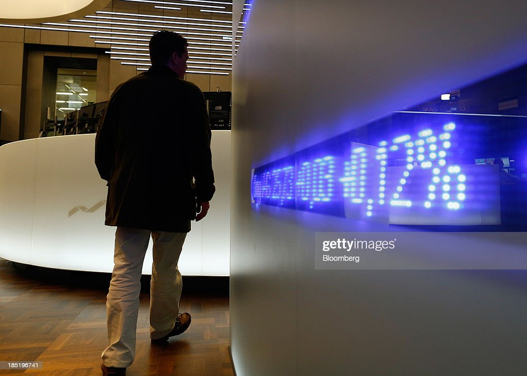 A trader passes an electronic display board at the Frankfurt Stock Exchange in Frankfurt, Germany, on Friday, Oct. 18, 2013. Global stocks rose for a third day, extending a five-year high, and copper climbed after China's economic growth quickened. Photographer: Ralph Orlowski/Bloomberg via Getty Images