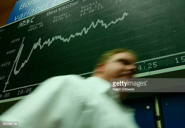 A trader passes the DAX index board during a trading session of the Frankfurt stock exchange July 28 2005 in Frankfurt Germany The German DaxIndex...