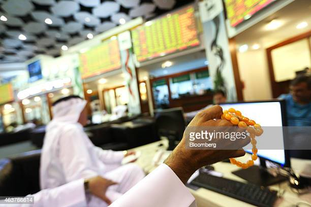 A trader plays with worry beads while monitoring share price information and other financial data on digital screens inside the Dubai Financial...