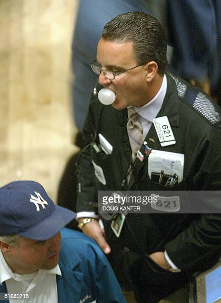A trader pops a bubble with his gum on the floor of the New York Stock Exchange 13 August 2002 The Dow Jones Industrial Average fell 20643 points to...