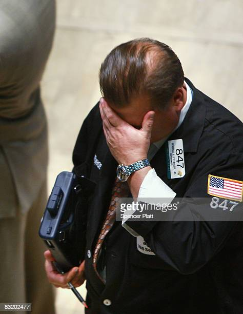 A trader puts his hand on his head on the floor of the New York Stock exchange October 9 2008 in New York City After a day in which the markets...