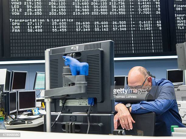 A trader reacts after the day's performance graph showed a sharp drop of the German DAX stock market index early today and a partial recovery later...