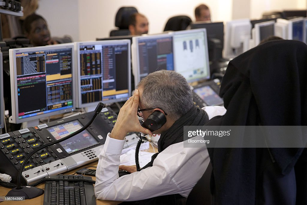 A trader reacts as he monitors financial data displayed on his computer screens at Aurel BGC's brokerage in Paris, France, on Monday, Nov. 12, 2012. European stocks fluctuated between gains and losses as finance ministers prepared to discuss Greek aid after the country's lawmakers approved the 2013 budget. Photographer: Balint Porneczi/Bloomberg via Getty Images