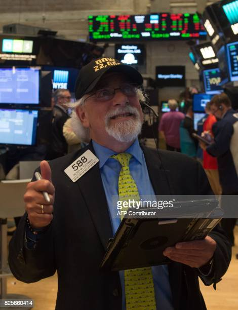 A trader reacts to the Dow closing above 22000 points on the floor at the closing bell of the Dow Jones Industrial Average at the New York Stock...