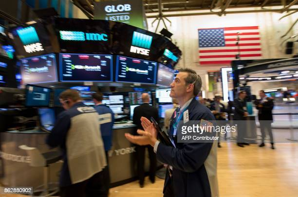 A trader reacts to the Dow closing above 230000 for the first time at the closing bell of the Dow Industrial Average at the New York Stock Exchange...